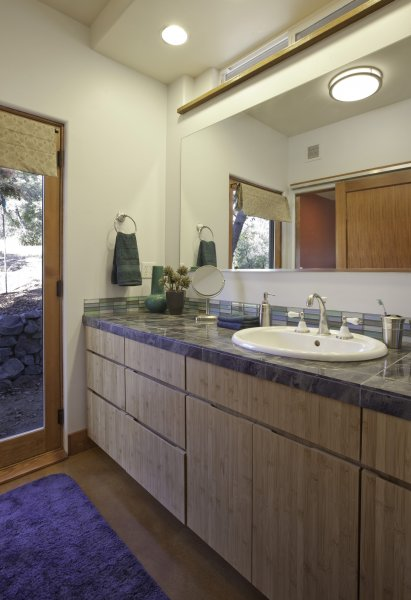 cabinets and a salvaged sink and faucet grace this green bathroom